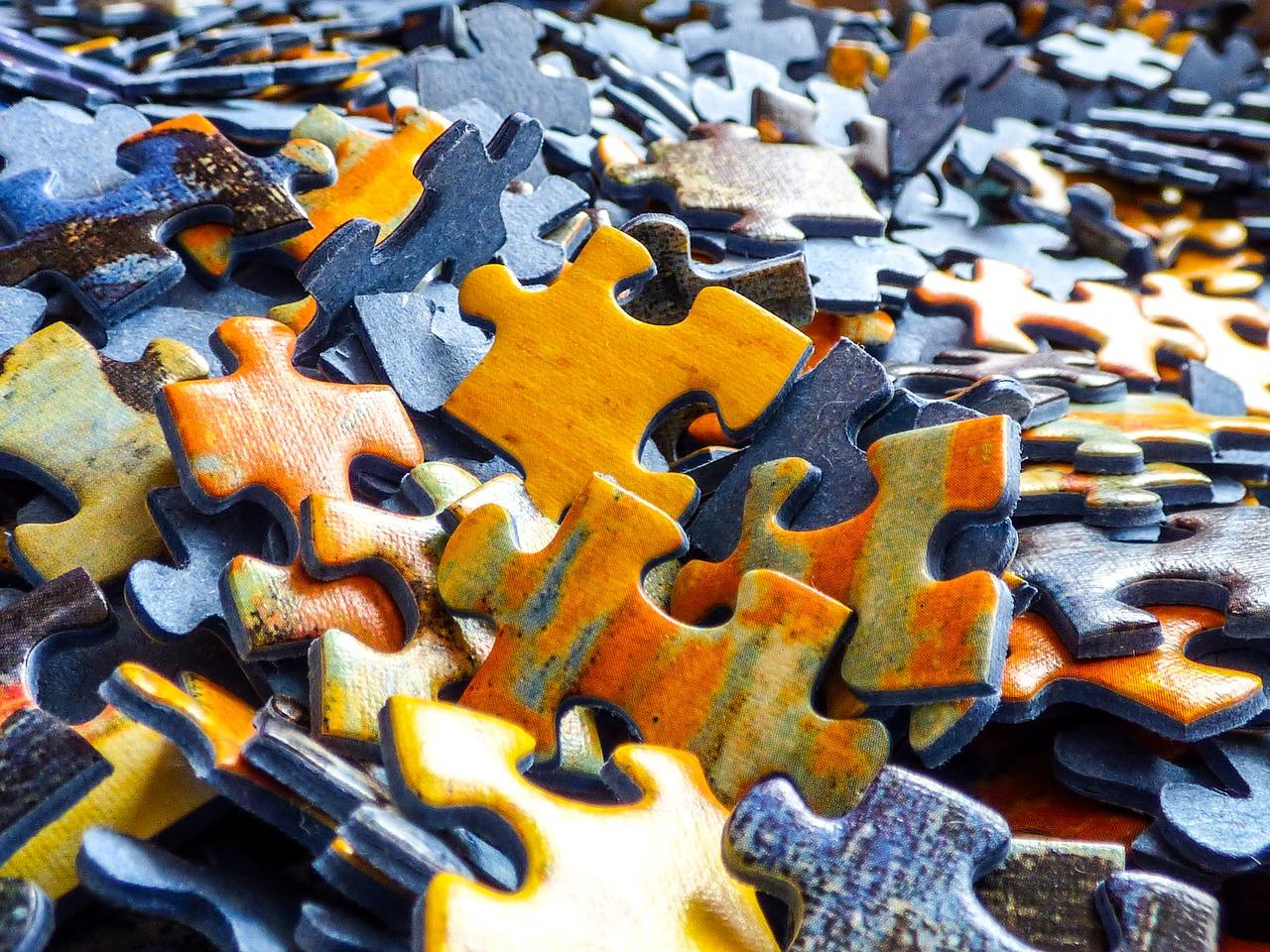 Großaufnahme vieler Puzzleteile, die ungeordnet auf einem Haufen liegen